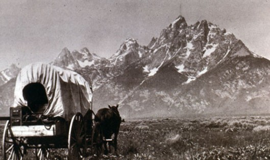 Real life and art. A settler's wagon under the Teton Range 1890s